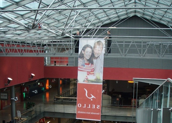 People hanging an advertisement on a gantry